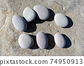 큰 바위 위에 일렬로 세워진 7 개의 작은 둥근 자갈 74950913