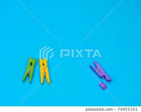 Violet wooden clothespin with fracture leg on blue background 74955101