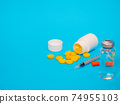 Syringe insulin with vial and yellow pills on blue background 74955103