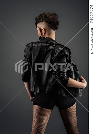Attractive young woman from back, with punk hairstyle, wearing leather jacket and fishnet stockings 74957374