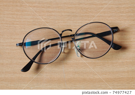 Broken Eye Glasses on the Wood Table in the Morning  74977427