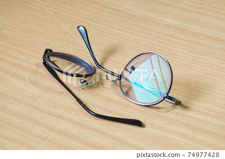 Broken Eye Glasses on the Wood Table in the Morning  74977428