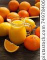Fresh orange juice in the glass jug 74978406
