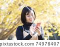 一個女人在秋天的公園中使用粉紅色的智能手機 74978407