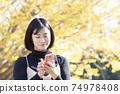一個女人在秋天的公園中使用粉紅色的智能手機 74978408