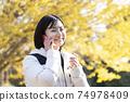 一個女人在秋天公園帶著微笑打電話 74978409