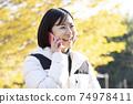 一個女人在秋天公園帶著微笑打電話 74978411