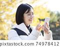 一個女人在秋天的公園中使用粉紅色的智能手機 74978412