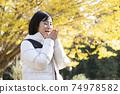 一個女人在秋天公園暖手 74978582