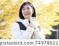 秋天的公園裡的白色智能手機的女人 74978621