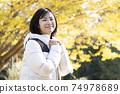 微笑的婦女看照相機在秋天公園 74978689