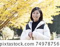 微笑的婦女看照相機在秋天公園 74978756