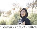站立在有鈴木的秋天公園的一名微笑的婦女在背景中 74978828