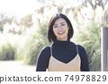 站立在有鈴木的秋天公園的一名微笑的婦女在背景中 74978829