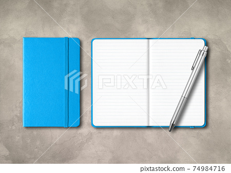 Blue closed and open lined notebooks with a pen on concrete background 74984716