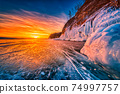 Sunset sky with natural breaking ice over frozen water on Lake Baikal, Siberia, Russia. 74997757