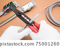 Electrical work A work scene where an electrician strips off the VVF cable insulation coating using a cable stripper 75001260
