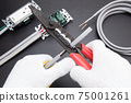 Electrical work A work scene where an electrician strips off the VVF cable insulation coating using a cable stripper 75001261