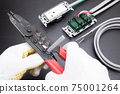 Electrical work A work scene where an electrician strips off the VVF cable insulation coating using a cable stripper Construction site 75001264