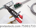 Electrical work A work scene where an electrician strips off the VVF cable insulation coating using a cable stripper 75001733