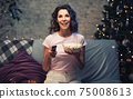 Young Beautiful woman stay home, during pandemic, spends his free time watching TV on couch at home, smiling munching popcorn and holding remote. Girl watching projector movies with popcorn in evening 75008613