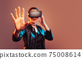 Young girl getting experience VR headset is using augmented reality eyeglasses being in virtual reality. Girl with hands up wearing virtual reality goggles. Woman touching air during VR experience 75008614