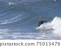 A surfer sportingly rides down a wave on a beach in Portugal on the Atlantic Ocean 75013476