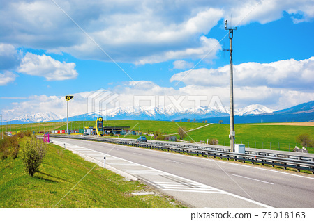 strba, slovakia - 01 MAY 2019: slovnaft gas station on a freeway. sunny scenery with green meadows beneath a blue sky with fluffy clouds. snow capped tatra mountains in the distance. wonderful journey 75018163