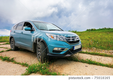 lypovets, ukraine - JUN 22, 2019: suv on the concrete roadside on top of the mountain runa. travel countryside concept. beautiful nature scenery in summer with dramatic sky 75018165