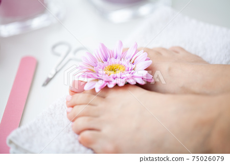 Cheerful Girl Doing Nails Making Pedicure Sitting In Bed Indoor. 75026079