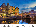 Amsterdam Netherlands, night city skyline of Dutch house at canal waterfront 75037165