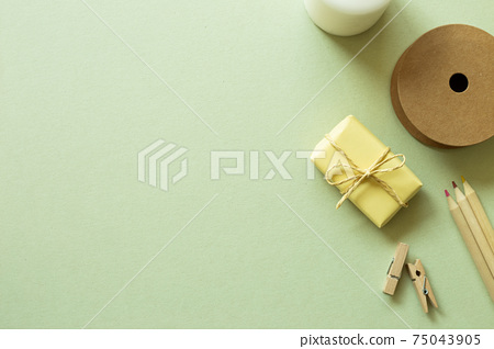 Gift box, string roll, wooden pencils, clips on green background. flat lay, top view, copy space 75043905