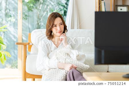 一位年輕的女士在客廳裡看電視 75051214