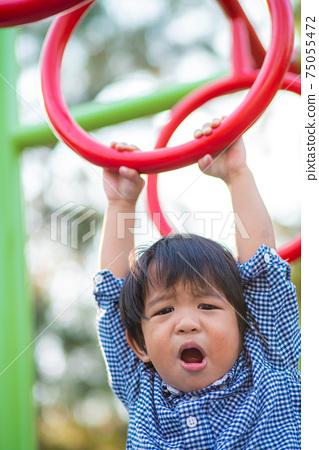 Happy asian child boy climb on playground bar in city park 75055472