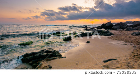 sea landscape at dawn. rocks on the sandy beach. clouds on the sky. summer vacation concept 75058535