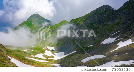 fagaras mountain landscape in summer. wonderful nature scenery with clouds on the peaks and snow in the valley. hills in grass and rocks. discover carpathins of romanian concept 75058536