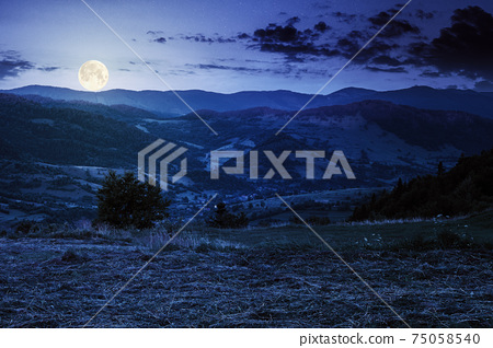 mountainous rural landscape at night. grassy meadow on top of a hill. clouds above the ridge in full moon light. view in to the distant valley 75058540