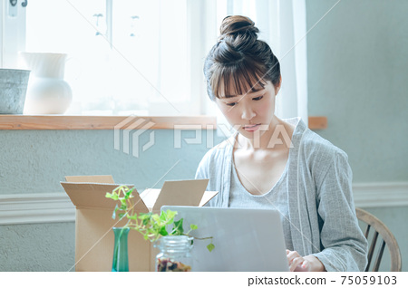 A woman using a computer to check luggage for online shopping at home 75059103