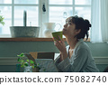 A young woman in pajamas spending her time at home 75082740