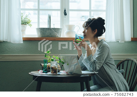 A young woman in pajamas spending her time at home 75082743