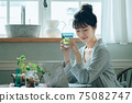 A young woman in pajamas spending her time at home 75082747
