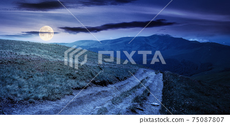 mountain landscape at night in spring. path through meadow in grass on the hill in full moon light. wonderful weather with fluffy clouds on the sky. borzhava ridge of carpathians 75087807