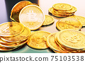 Cryptocurrency Bitcoin golden coins spilling on the table. 75103538