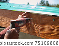 Unsafe Male Roofer Workman Using Electric Screwdriver Install Tile on Roof of New House in the Construction Site with no Protection 75109808