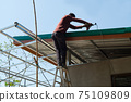 Unsafe Male Roofer Workman Using Electric Screwdriver Install Tile on Roof of New House in the Construction Site with no Protection 75109809