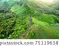 Aerial view of Beautiful sky road over top of mountains with green jungle in Nan province, Thailand. 75119638
