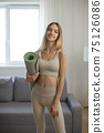 Sporty Woman with Yoga Mat at Home 75126086
