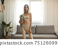 Sporty Woman with Yoga Mat at Home 75126099