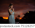 Half-woman standing in the park at dusk and posing asking 75126257