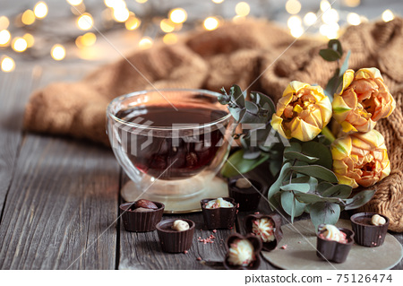 Cozy composition with a cup of tea, sweets, knitted element and flowers close up. 75126474